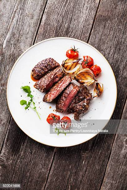 Sliced medium rare grilled Beef steak Ribeye with grilled onions