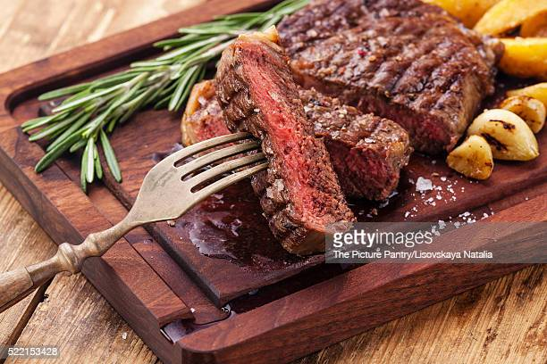 Sliced medium rare grilled Beef steak Ribeye with roasted potato