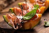 sliced melon with ham basil leaves