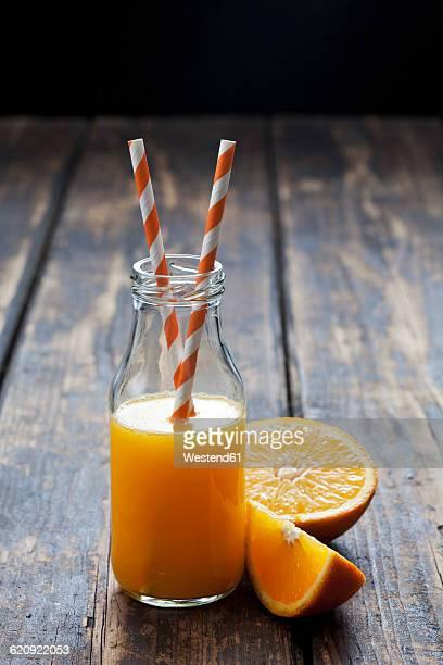 Sliced orange and bottle of orange juice on wood