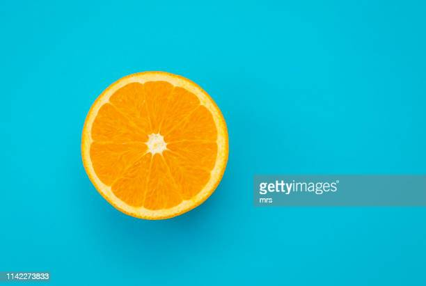 sliced orange on blue background - aliment en portion photos et images de collection