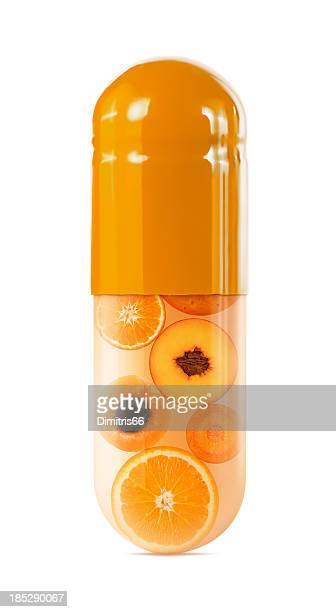 Sliced oranges in oversized capsule on white