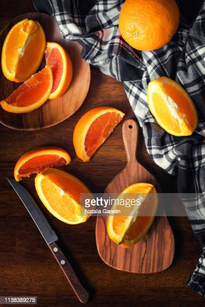 sliced oranges on wooden table - navel orange stock photos and pictures