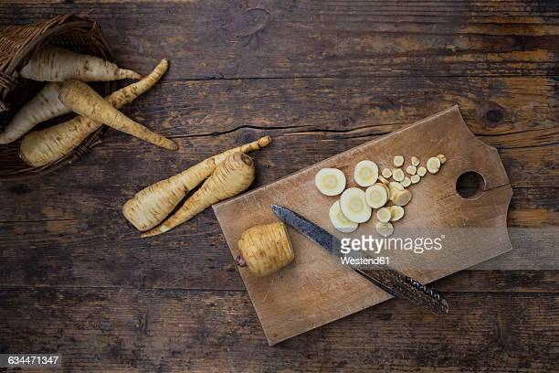 Sliced organic parsnips and pocket knife on chopping board