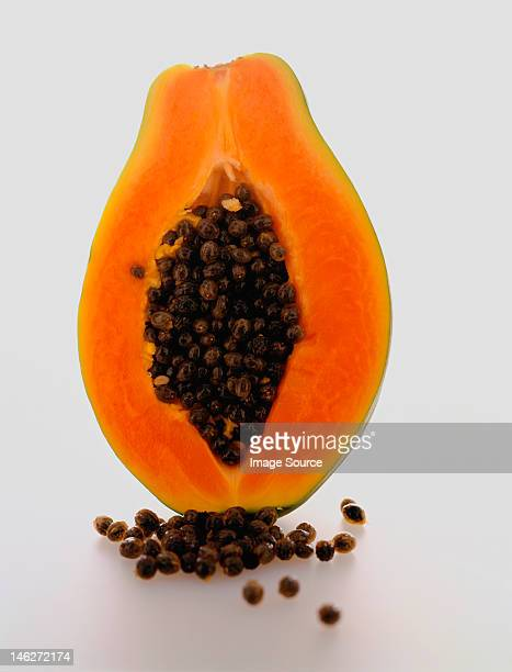 sliced papaya against white background - papaya stock photos and pictures