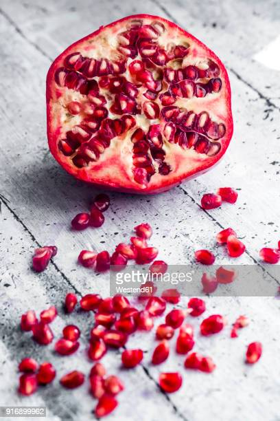 Sliced pomegranate and pomegranate seed on wood