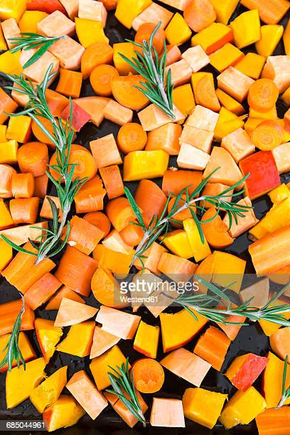 sliced pumpkin, carrots and sweet potatoes with twigs of rosemary on baking tray - sweet potato stock pictures, royalty-free photos & images