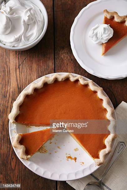 Sliced pumpkin pie on wood table, from above