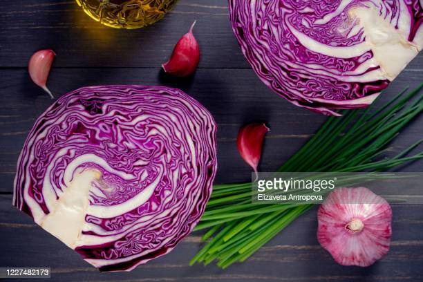 sliced purple cabbage on a wooden table with garlic, onions, top view - chopping stock pictures, royalty-free photos & images
