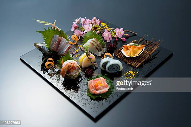 Sliced raw fishes on a tray, high angle view, black background, Japan