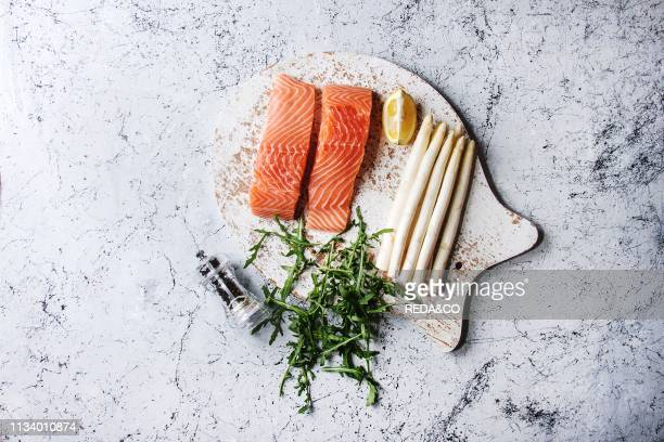 Sliced raw uncooked salmon fillet on wooden chopping board as fish shape with ingredients for cooking dinner arugula white asparagus over white...