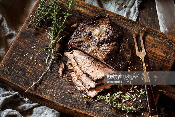 Sliced roast beef, rosemary, thyme and sea salt on chopping board