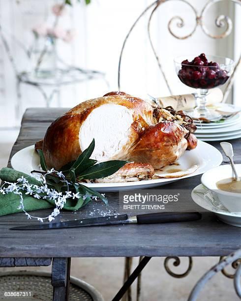 Sliced roast chestnut turkey on patio christmas table