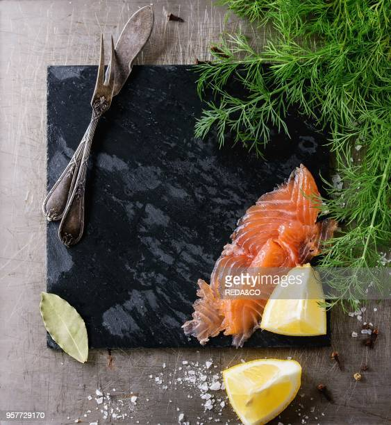 Sliced salted salmon fillet fresh dill sliced lemon and sea salt with empty black stone slate board and vintage cutlery over textured iron background...