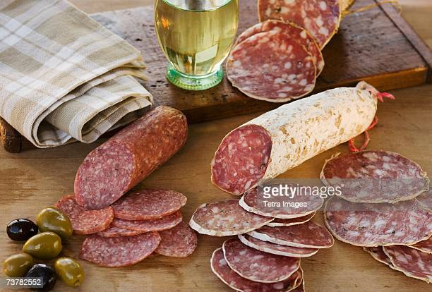 Sliced sausages and olives on table