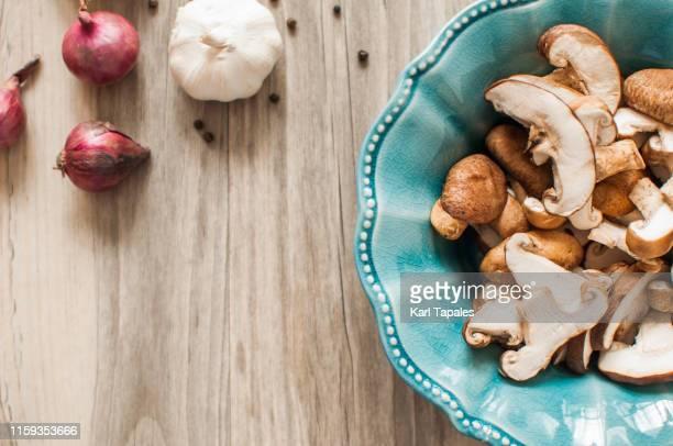 sliced shiitake mushroom on a rustic setting - fungo foto e immagini stock