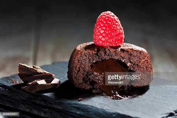 Sliced small chocolate tart with melted chocolate filling garnished with raspberry