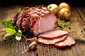 Sliced smoked gammon on a wooden  table with addition of fresh  herbs and aromatic spices.