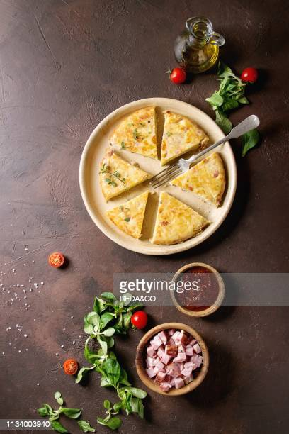 Sliced spanish potato omelette tortilla with bacon served in ceramic plate with sauce and ingredients above over dark brown texture background Top...