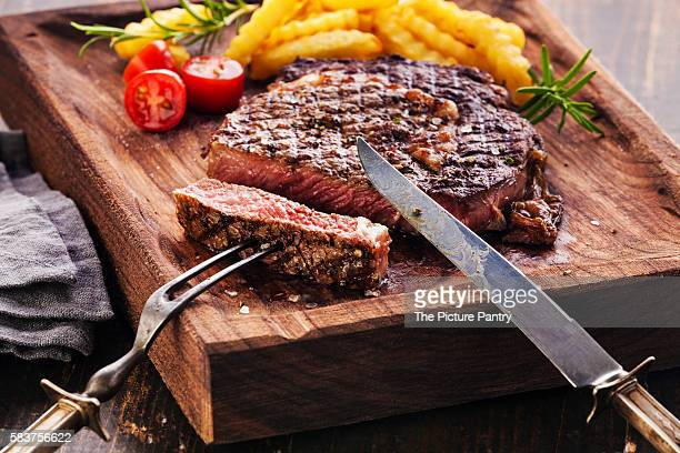 Sliced Steak Ribeye with french fries on serving board block on wooden background