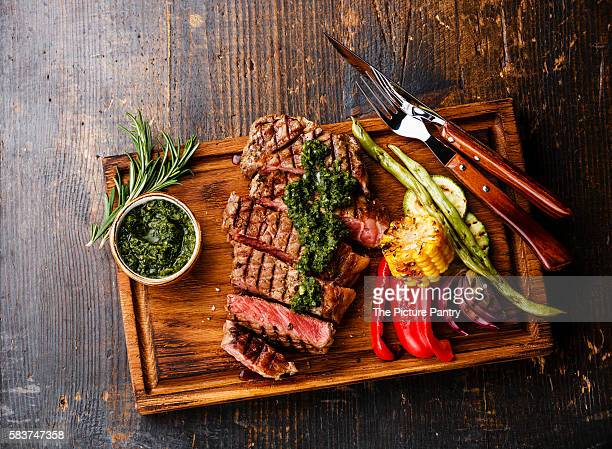 sliced striploin steak with chimichurri sauce and grilled vegetables on cutting board on dark background - チミチュリ・ソース ストックフォトと画像