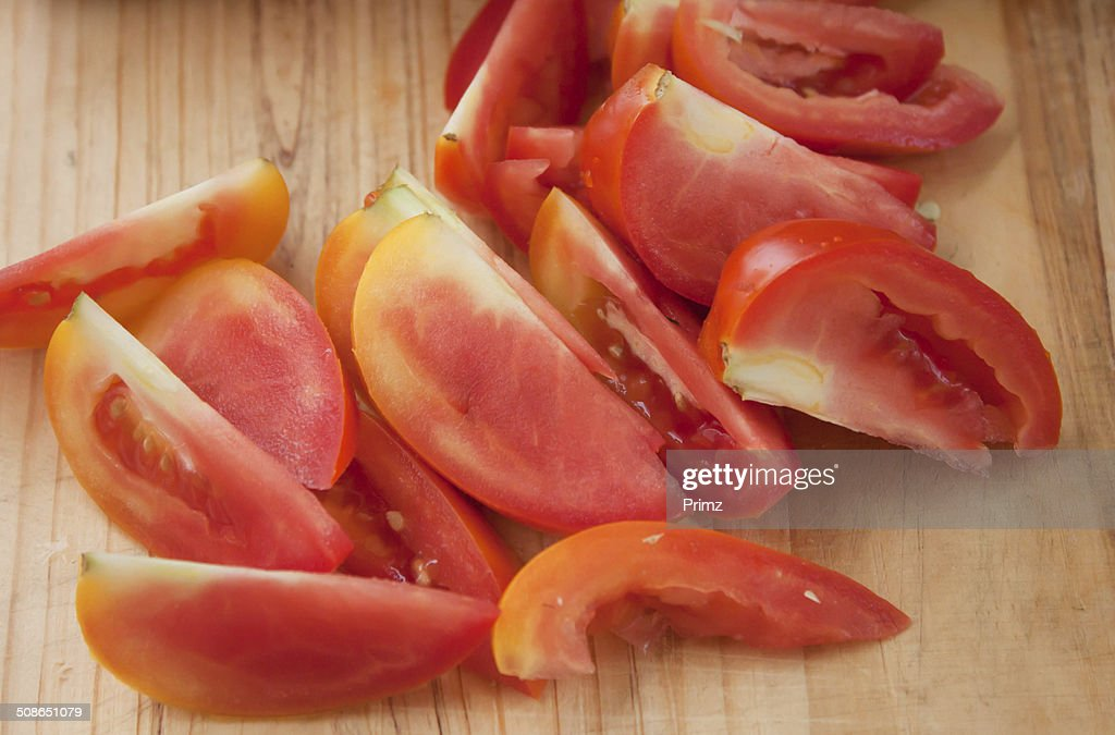 Sliced ​​tomato paste on a wooden cutting board. : Stock Photo