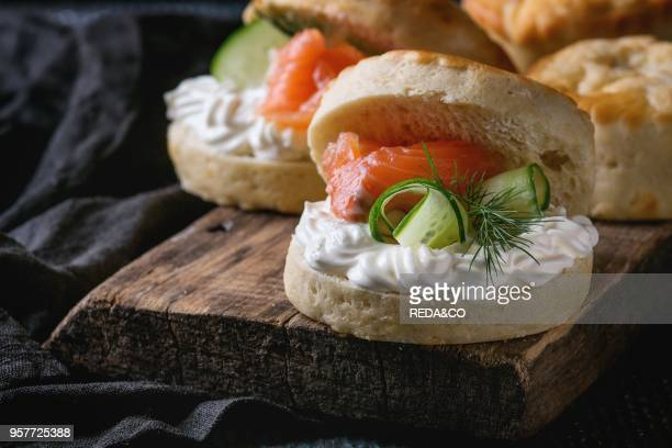 Sliced traditional english cheese scones with smoked salmon creme cheese and fresh cucumber served with whole scones on wooden chopping board over...