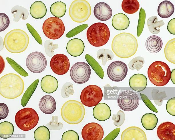 Sliced vegetables on illuminated white surface, full frame