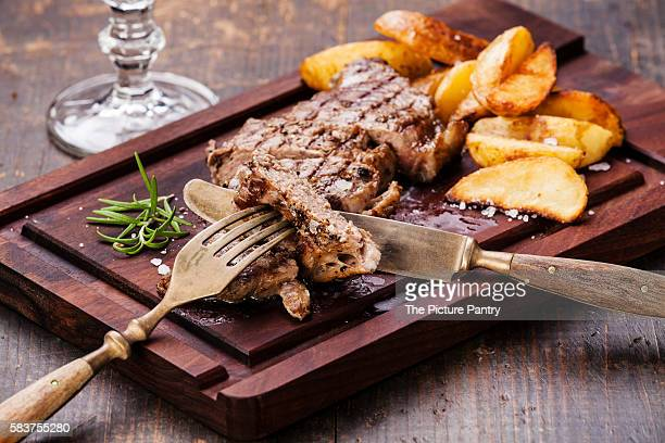Sliced well done grilled New York steak with roasted potato wedges on cutting board on wooden background
