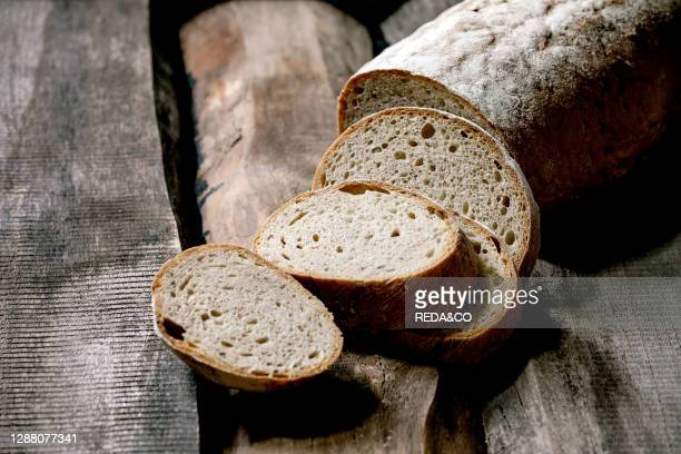 Sliced whole grain artisan rye-wheat organic bread over old wooden background.