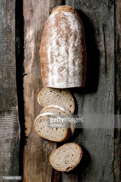 Sliced whole grain artisan rye-wheat organic bread over old wooden background. Flat lay, space.
