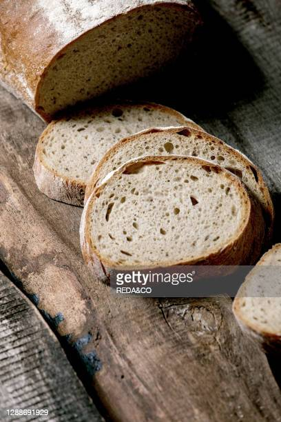 Sliced whole grain artisan rye-wheat organic bread over old wooden background. Close up.