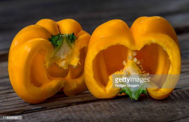 sliced yellow bell pepper showing the thickness of the fruit and the pips contained inside. - yellow bell pepper stock pictures, royalty-free photos & images
