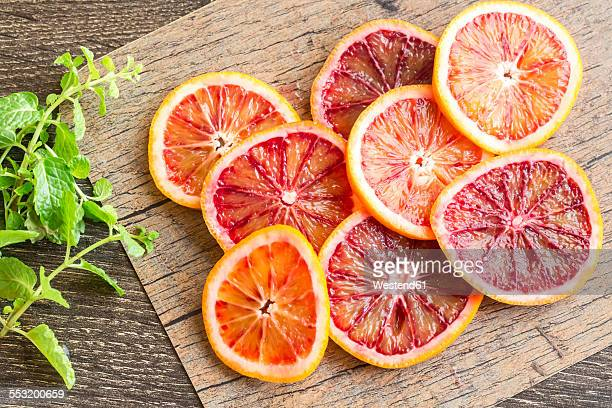 Slices of blood orange and mint leaves on wood