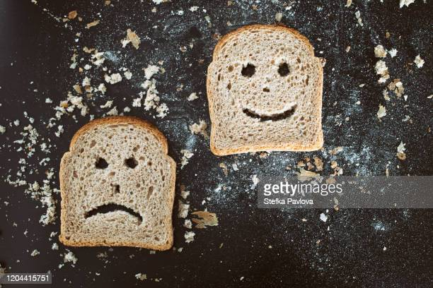slices of bread toast with happy and sad human face representations - gluten free bread stock pictures, royalty-free photos & images