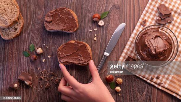 slices of bread with chocolate cream nuts and knife. - nutella stock pictures, royalty-free photos & images