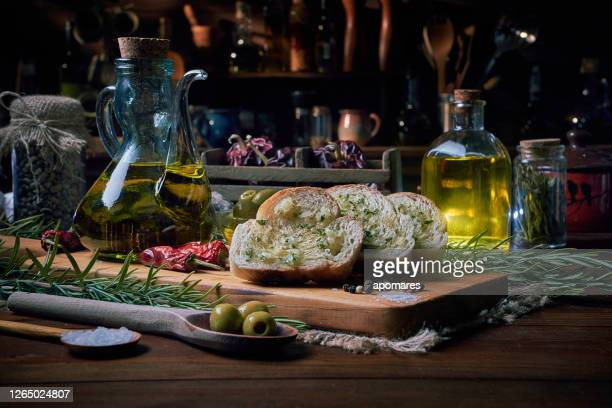 slices of bread with olive oil and garlic appetizers in a rustic kitchen - italian food stock pictures, royalty-free photos & images