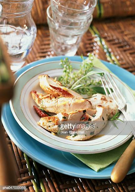 Slices of chicken with tarragon on plate with tableware