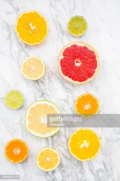 Slices of different citrus fruits on white marble