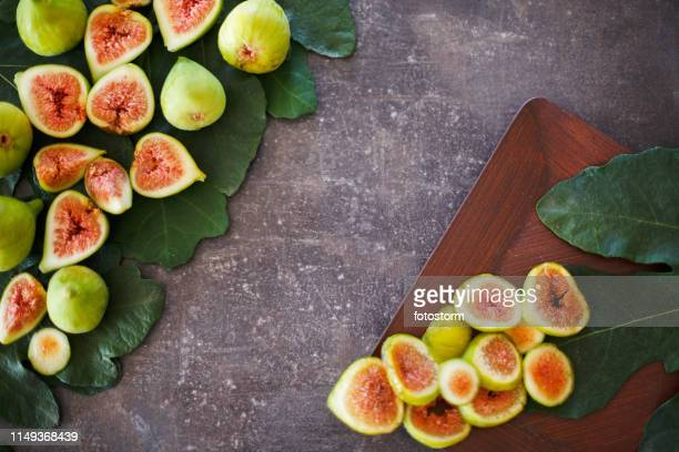 slices of digs on wooden table - fig stock pictures, royalty-free photos & images