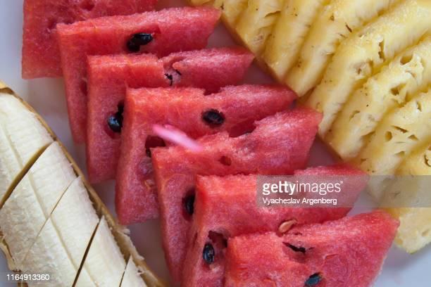 slices of fresh watermelon, banana and pineapple - argenberg imagens e fotografias de stock