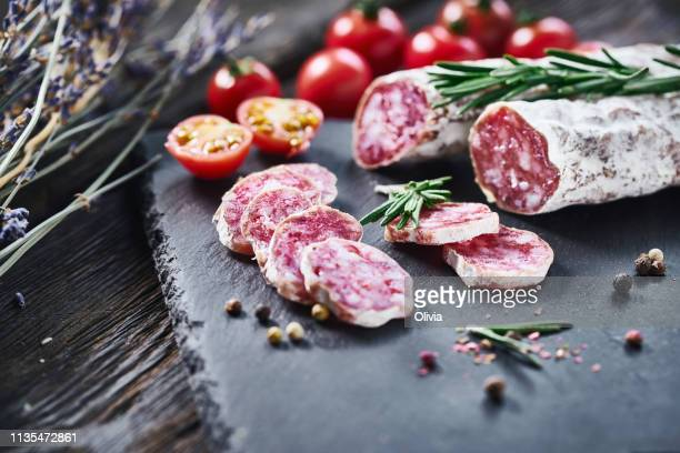 slices of fuet salami with baguette - salami stock pictures, royalty-free photos & images