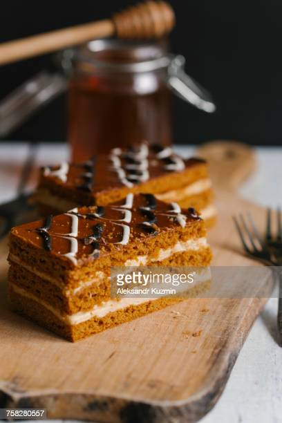 Slices of layer cake on cutting board with honey