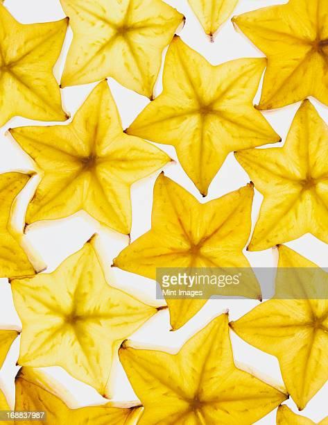 Slices of organic starfruit on white background