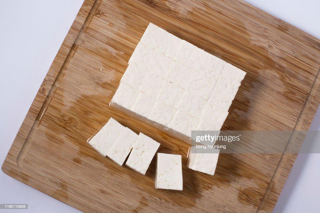 Slices of raw tofu on cutting board : Stock Photo