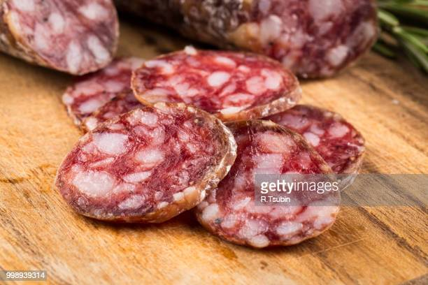slices of salami on a wood board as a background - salami stock pictures, royalty-free photos & images