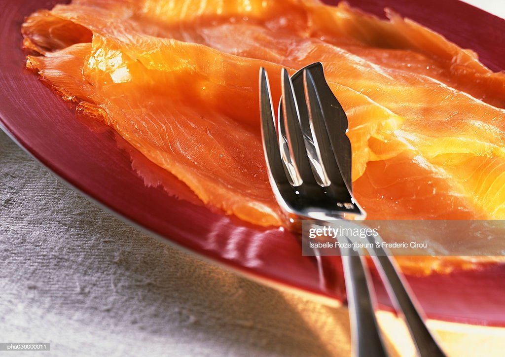 Slices of smoked salmon on plate with silverware, extreme close-up : Stockfoto