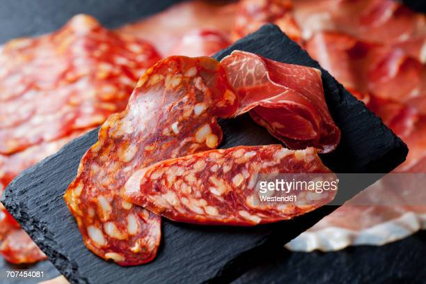 slices of spanish salami and slice of italian ham on slate - pepperoni stock photos and pictures