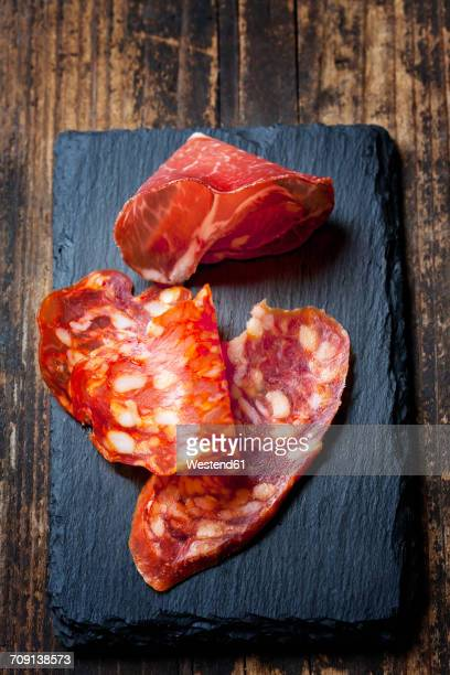 Slices of Spanish salami and slice of Italian ham on slate