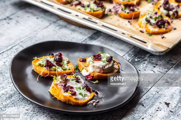 Slices of sweet potato with cream cheese, ramson cream, goat cheese, cress and cranberries